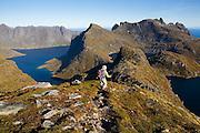 Parmenter Welty hikes down a ridge (below Hermannsdalstinden) high above Reinefjorden on Moskenesoya, Lofoten Islands, Norway.