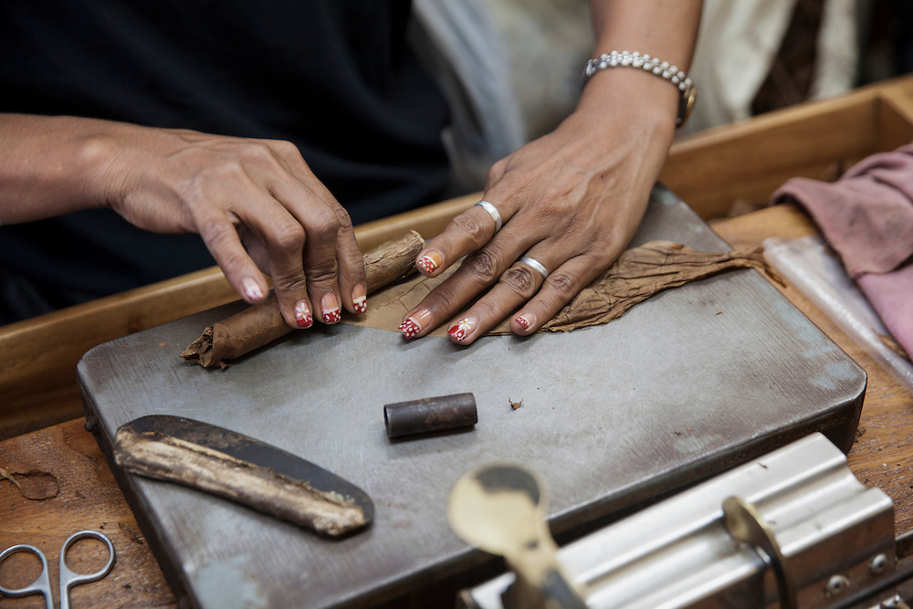 A worker at the 'El Laguito', Cohiba's manufacturing facility in Havana, rolls up a cigar during her working shift.