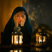 Woman under a veil in front of candles.