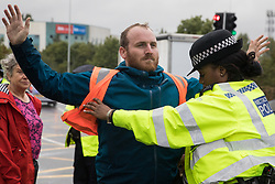 Colnbrook, UK. 27th September, 2021. Insulate Britain spokesman Liam Norton is arrested after a slip road from the M25 at Junction 14 close to Heathrow is blocked by Insulate Britain as part of a campaign intended to push the UK government to make significant legislative change to start lowering emissions. The activists are demanding that the government immediately promises both to fully fund and ensure the insulation of all social housing in Britain by 2025 and to produce within four months a legally binding national plan to fully fund and ensure the full low-energy and low-carbon whole-house retrofit, with no externalised costs, of all homes in Britain by 2030.