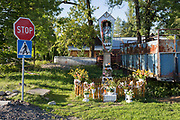 A landscape of a Polish village Catholic shrine that stands next to a rusting agricultural trailer on a grassy verge, on 17th September 2019, in Witow, near Zakopane, Malopolska, Poland.