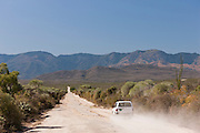 An offroad vehicle driving along a long, dusty, broken road towards Fort Dauphin, Madagascar