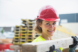 Female construction worker carrying wooden plank at building site, Munich, Bavaria, Germany