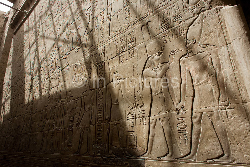 Sunlit hieroglyphs in the dark recesses of the ancient Egyptian Luxor Temple, Nile Valley, Egypt. The temple was built by Amenhotep III, completed by Tutankhamun then added to by Rameses II. Towards the rear is a granite shrine dedicated to Alexander the Great and in another part, was a Roman encampment. The temple has been in almost continuous use as a place of worship right up to the present day.