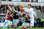 Swansea's Fernando Llorente ® challenges Burnley's Michael Keane (l) and Matthew Lowton (c). Premier league match, Swansea city v Burnley at the Liberty Stadium in Swansea, South Wales on Saturday 4th March 2017.<br /> pic by  Carl Robertson, Andrew Orchard sports photography.