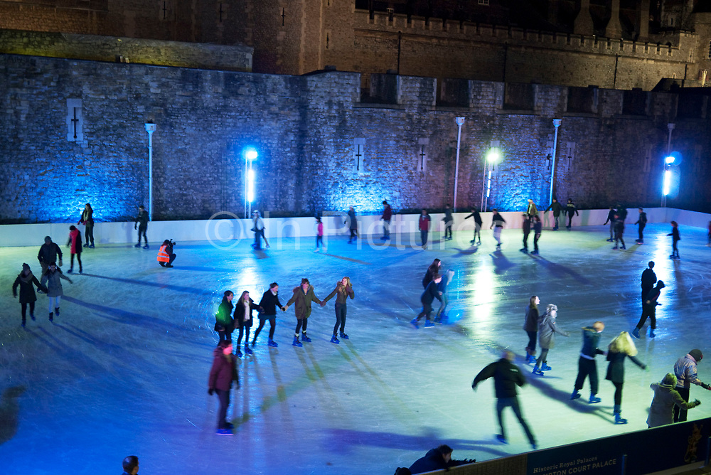 Ice skating rink at the Tower of London. People come here each year as a temporary rink is put up for the Christmas period. Here, a group of friends holding hands skate around together in the evening with the rink lit up for the night sessions.
