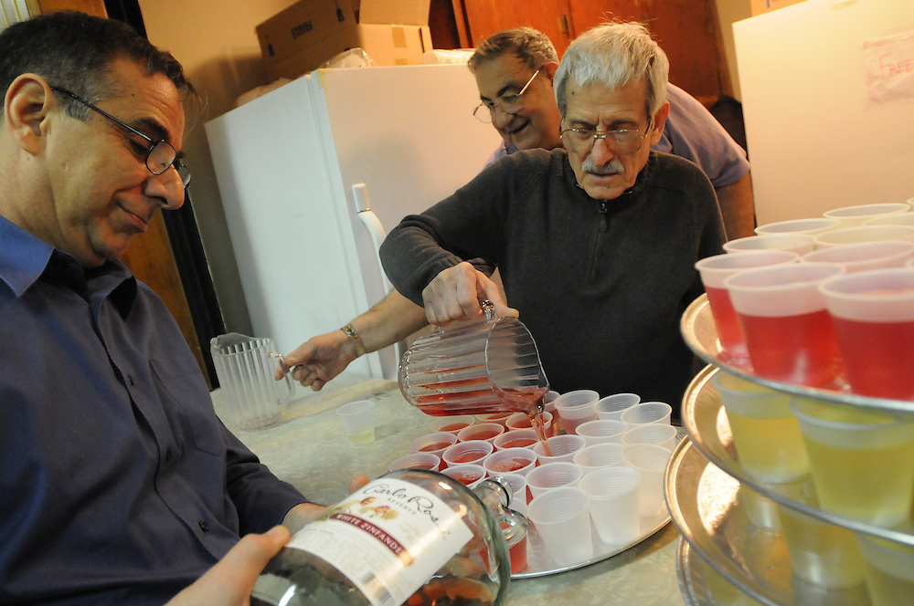 Our Lady of Pompeii Parishioners Vince Gemino (L to R), Jimmy DiFiore and Giovanni Cesario ready the wine for St. Joseph's Table. The annual Italian feast commemorates the end of drought and famine following the prayers of hungry Sicilians to Saint Joseph the Protector.