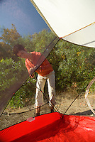 A young woman sets up a tent at a campsite in southern California.