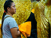 31 MAY 2017 - CHACHOENGSAO, THAILAND: A woman prays before wrapping a statue of the Buddha in orange cloth at Wat Sothon (also spelled Sothorn) in Chachoengsao, Thailand. The temple is one of the largest and most visited in Thailand. People make merit by paying to wrap the Buddha statues in orange robes. The temple is most famous because people leave hard boiled eggs as an offering at the temple. They ask for business success or children and leave hundreds of hard boiled eggs.      PHOTO BY JACK KURTZ