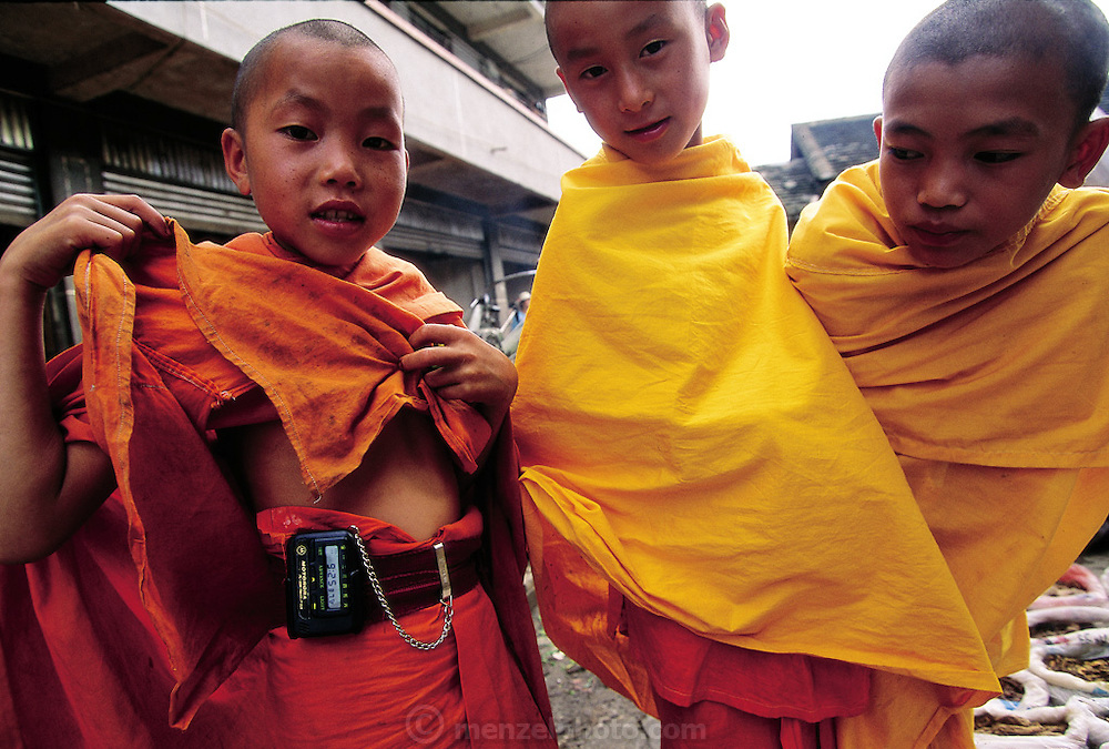 """As a preadolescent Buddhist monk walks through a market with two other young monk friends in the southern province of Yunnan; he proudly displays his fake pager; a coveted toy from """"Motorora; Ching Menghan Sunday Market; Yunnan; China. (Man Eating Bugs page 84; 85)"""