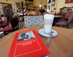 Detail of coffee and political book about Lenin in Cafe Tasso on Karl Marx Allee in former east Berlin in Germany