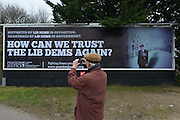 """© Licensed to London News Pictures. 25/02/2013. Eastleigh, UK. A man takes a picture after Brian Leggett, UK spokesperson for the International Consortium of British Pensioners  (ICBP) launches a billboard campaign in Eastleigh, Hampshire, today 25th February 2013. the """"How Can We Trust The Lib Dems Again"""" claims that pensioners who live abroad are unlikely to receive their full state pensions. Photo credit : Stephen Simpson/LNP"""
