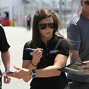 NASCAR Sprint Cup driver Danica Patrick (10) is seen signing autographs for her fans, in the garage area during the NASCAR Coke Zero 400 Sprint practice session at the Daytona International Speedway on Thursday, July 4, 2013 in Daytona Beach, Florida.  (AP Photo/Alex Menendez)
