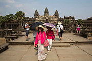Two Asian female visitors walk away from Angkor Wat temple Angkor Wat Siem Reap, Cambodia.  Angkor Wat is Cambodia's main tourist destination.