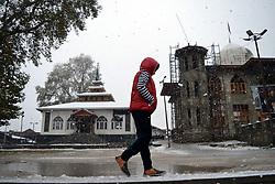 A Kashmiri young boy walks briskly amid snowfall in Srinagar, the summer capital of Indian controlled Kashmir. Kashmir witnessed its first snowfall.