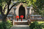Myanmar, young apprentice priests with red parasol