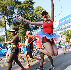 July 4, 2018 - Atlanta, GA, USA - Breast cancer survivor Ann Marie Vollmar gets some air crossing the finish line in the AJC Peachtree Road Race on Wednesday, July 4, 2018, in Atlanta. (Credit Image: © Curtis Compton/TNS via ZUMA Wire)