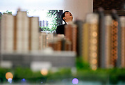 A man looks up from behind model of new apartment buildings at a real estate fair in Shanghai, China on 15 March, 2009.  For the past decade, Shanghai has underwent the largest reconstruction in recorded history, over 20 million square meters of land, approximately a third of Manhattan, were developed between year 200 and 2005 alone. Despite that however, housing prices have seen a rapid increase, putting the prospect of owning a decent sized home out of the reach of ordinary Chinese citizens, especially middle to low income families.