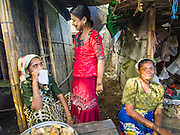 09 NOVEMBER 2014 - SITTWE, RAKHINE, MYANMAR: Rohingya Muslim women in a market in a Rohingya Muslim IDP camp near Sittwe. After sectarian violence devastated Rohingya communities and left hundreds of Rohingya dead in 2012, the government of Myanmar forced more than 140,000 Rohingya Muslims who used to live in and around Sittwe, Myanmar, into squalid Internal Displaced Persons camps. The government says the Rohingya are not Burmese citizens, that they are illegal immigrants from Bangladesh. The Bangladesh government says the Rohingya are Burmese and the Rohingya insist that they have lived in Burma for generations. The camps are about 20 minutes from Sittwe but the Rohingya who live in the camps are not allowed to leave without government permission. They are not allowed to work outside the camps, they are not allowed to go to Sittwe to use the hospital, go to school or do business. The camps have no electricity. Water is delivered through community wells. There are small schools funded by NOGs in the camps and a few private clinics but medical care is costly and not reliable.  PHOTO BY JACK KURTZ
