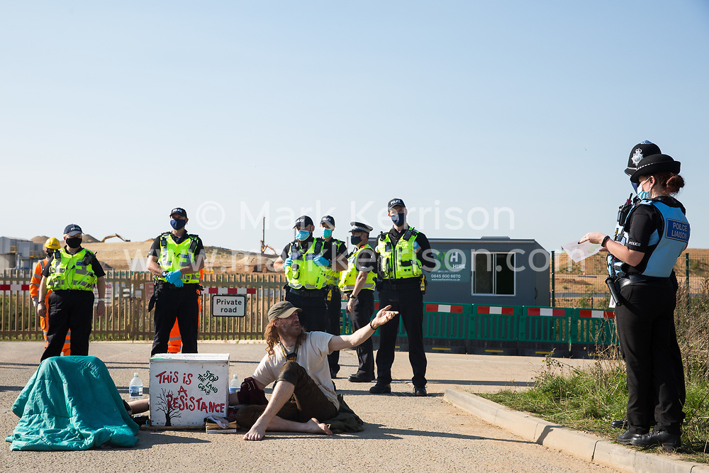 West Hyde, UK. 14th September, 2020. Environmental activists from HS2 Rebellion query the ownership of land with Hertfordshire Police officers whilst using a lock-on arm tube to block a gate to the South Portal site for the HS2 high-speed rail link. Anti-HS2 activists blocked two gates to the same works site for the controversial £106bn rail link, one remaining closed for over six hours and another for over nineteen hours.