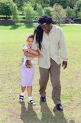 Single father walking across park with young daughter,
