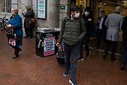 As the Coronovirus pandemic takes hold across the UK, with health authorities reporting cases rising from 25 to 87 in a single day, and resulting in the UKs chief medical officer Prof Chris Whitty announcing that an epidemic in the UK was highly likely, a couple wearing surgical masks walk past Evening Standard headlines outside Embankment Underground station, on 4th March 2020, in London, England.