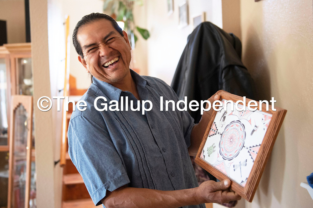 Davis Coonis, Zuni Pueblo Artwalk featured artist laughs as he holds up a piece he drew while in jail, the supplies were limited he says referring to the few colors used.