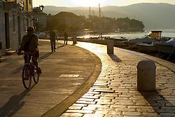 Europe, Croatia, Dalmatia, Hvar Island, Stari Grad town.  Promenade by harbor at sunset.