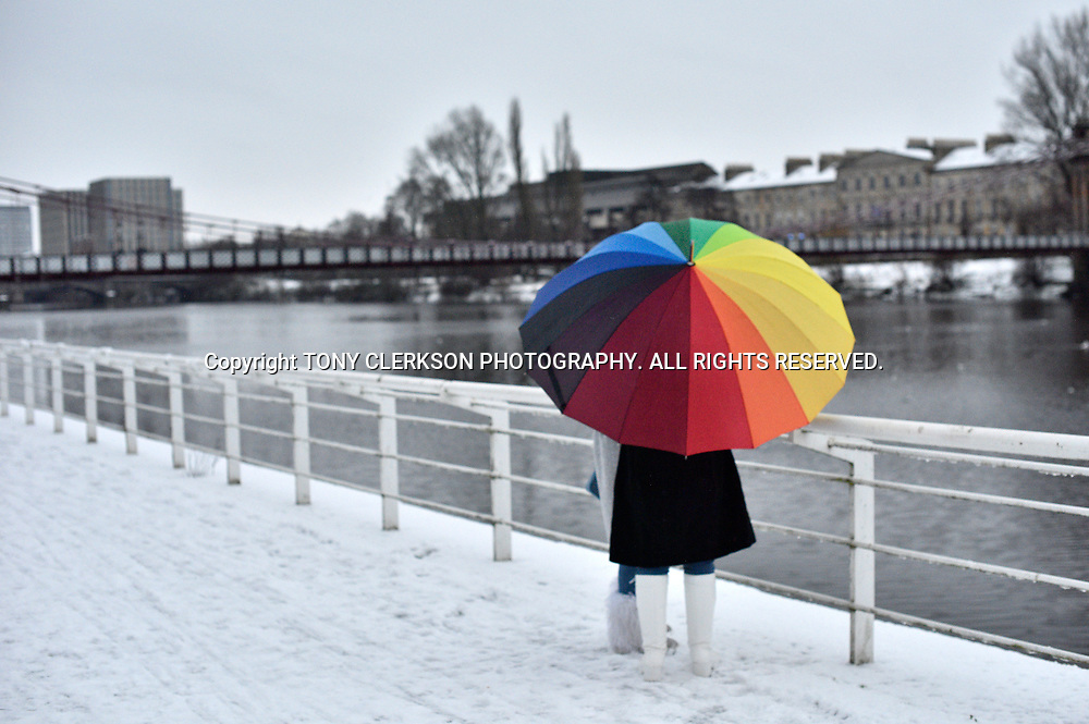 A bright umbrella lights up snowy scene by the River Clyde