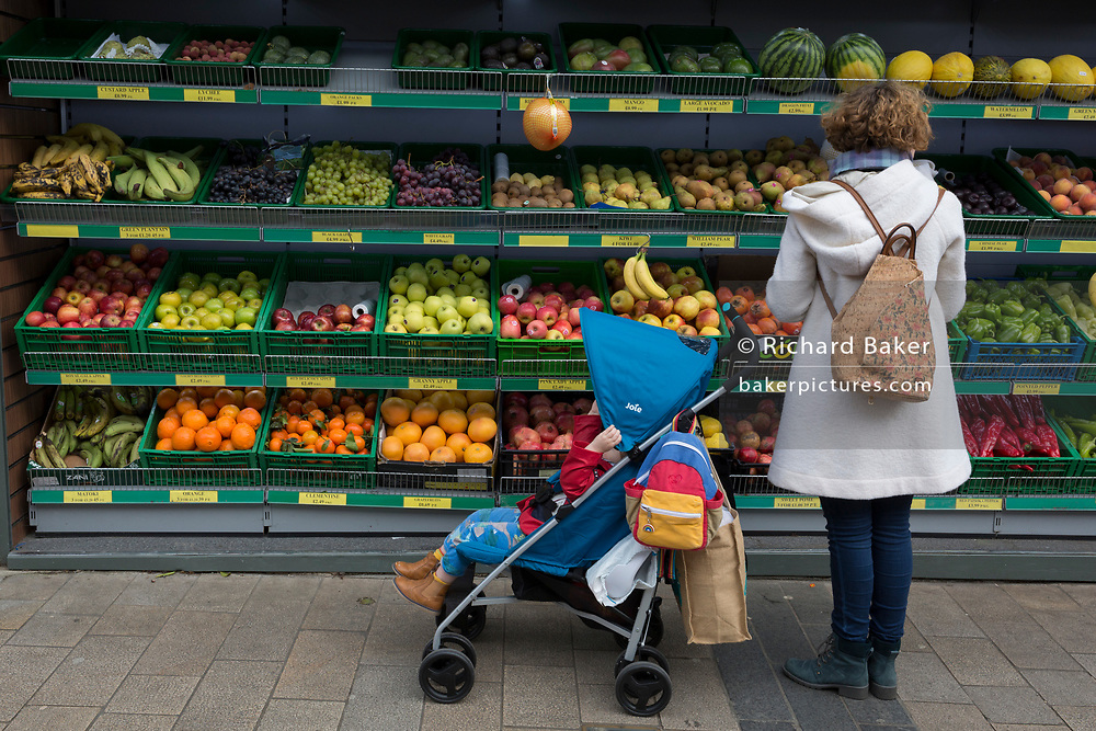 A mother and child stop to choose nutritious fruit and veg from the shelves outside a shop in Bromley town centre, on 3rd February 2020, in London, England