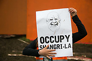 A child holds up a joke poster saying occupy Shangri-la with the face of the festivals owner on, Michael Eavis at Shangri-la at the Glastonbury Festival 21th July 2016, Somerset, United Kingdom. Shangri-la is a venue at the festival with  art and politics mixed with tunes and all night club nights. Work getting the festival ready takes weeks and in the days up to the festival starts work is frantic.  The Glastonbury Festival runs over 3 days and has 3000 acts, including music, art and performance and approx. 150.000 attend the anual event.