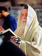 An old jewish man reads from the scriptures as he prays at the Wailing Wall in Jerusalem, Israel
