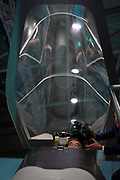 A visitor to the BAE Systems exhibition hall is handed a helmet in a mock-up of the Tempest fighter, a replacement for the Typhoon, in the companys exhibition hall at the Farnborough Airshow, on 18th July 2018, in Farnborough, England.