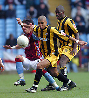 Photo: Dave Linney.<br />Aston Villa v Port Vale. The FA Cup. 28/01/2006.Port Vales George Abbey(C) holds off a challenge from Milas Baros