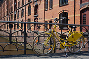 bike on railing by Harbour Pier buildings (Landungsbruecken)  on the Elbe river, historic industrial architecture, Hamburg, Germany.
