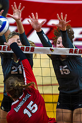 BLOOMINGTON, IL - September 14: Monica Miller strikes the ball over the net to Kathryn Wesolich and Kristina Fisher during a college Women's volleyball match between the ISU Redbirds and the University of Central Florida (UCF) Knights on September 14 2019 at Illinois State University in Normal, IL. (Photo by Alan Look)