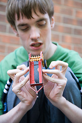 Teenage boy with Autism playing with toy plough,