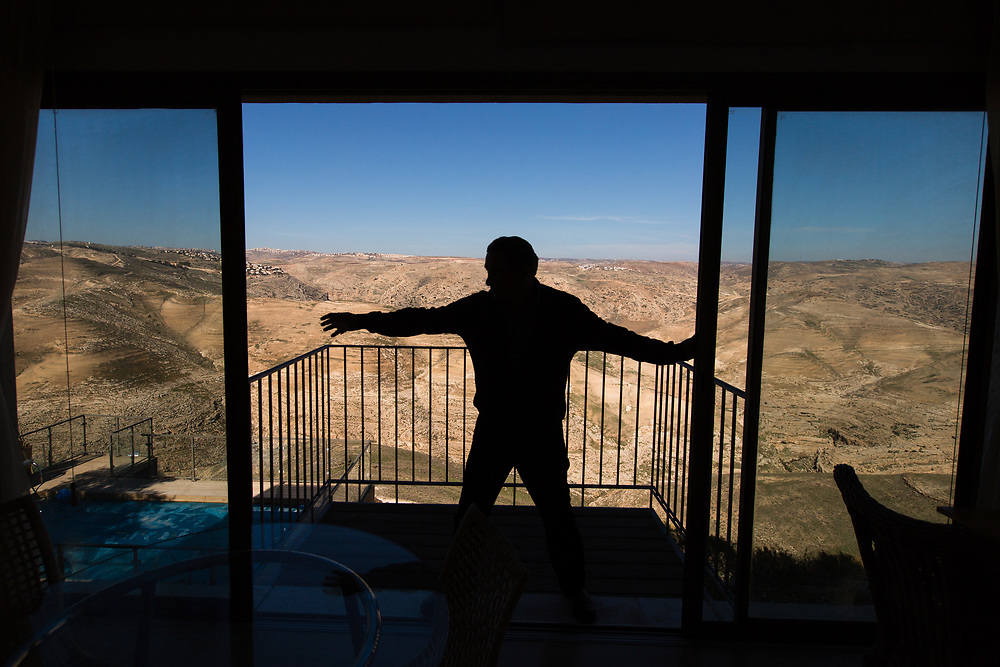 Israeli Jewish settler Igal Canaan is silhouetted as he closes the glass doors leading to a terrace overlooking Wadi Qelt (Nahal Prat in Hebrew) at his bed and breakfast 'Nof Canaan' which is advertised on Airbnb international home-sharing site and rental listings service, in the West Bank Jewish settlement of Nofei Prat, on January 28, 2016.