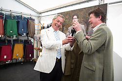 © Licensed to London News Pictures. 31/07/2015. Leeds , UK . NIGEL FARAGE at the Ratcatcher marquee given a bottle by Charles Wall at the CLA GameFair ( Country Landowners Association ) at Harewood House in Yorkshire . Photo credit: Joel Goodman/LNP