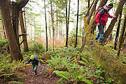 Liana and Parmenter Welty hike down logs and up the trail from Third Beach, Olympic National Park, Washington.