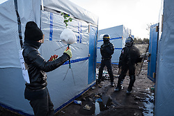 © London News Pictures. Calais, France. 07/03/16. A man shows a snowman to two bemised French riot police officers. French authorities are evicting and demolishing the southern half of the Calais 'Jungle' camp, which charities estimate to contain 3,500 people. . Photo credit: Rob Pinney/LNP