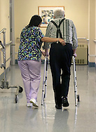 Certified Nursing Assistant 2 Yolanda Samuel helps Blake Tyrrell walk down the hall at Middletown Park Manor on Jan. 20, 2006.
