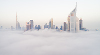 Aerial view of Dubai's skyscrapers in the clouds, U.A.E.