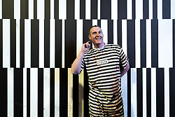 © Licensed to London News Pictures . 01/11/2015 . Manchester , UK . A man wearing a horizontally striped prison convict's costume in front of a vertically striped billboard . Halloween revellers , wearing make up and costumes , out and about in Manchester City Centre . Photo credit : Joel Goodman/LNP