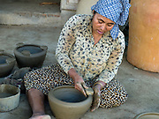 A Hindu Cham woman making a ceramic barbeque using a traditional method in the famous pottery village of Bau Truc in Central Vietnam. Cham potters do not use a wheel to make pots, instead clay is pressed into shape using the hands. Layers of clay are added to the original piece and the potter moves around the object, pressing the clay into the desired shape. They are then put directly in the sun and completely bone dried, making them ready to be fired. Firing is done in an open pit with temperatures going up to 800 degree Celcius. The pots are arranged together and covered with layers of rice straw, which is set on fire.