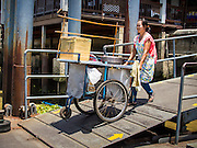 24 AUGUST 2014 - BANGKOK, THAILAND: A food vendor pushes her cart down to a cross river ferry on the Chao Phraya River. She was going from the Bangkok side of the river to the Thonburi side.      PHOTO BY JACK KURTZ