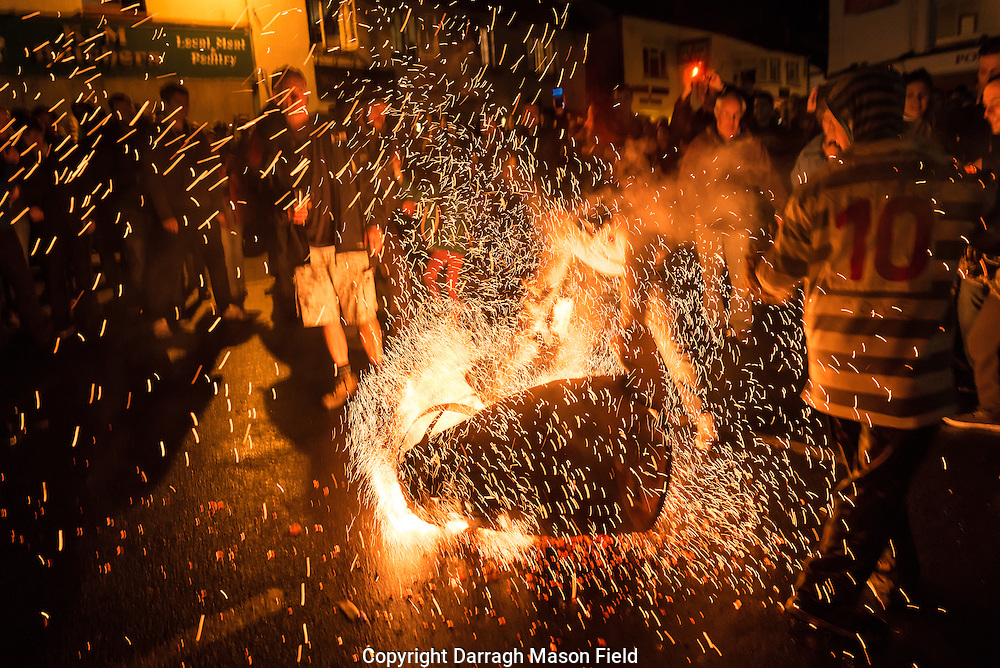 With a crash of sparks a fire a barrel explodes as it hits the street.