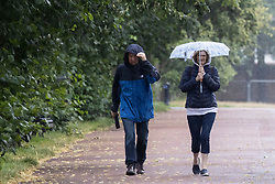© Licensed to London News Pictures. 08/08/2021. London, UK. A woman uses an umbrella to shelter from rain in Greenwich Park in South East London. A yellow weather warning for thunderstorms is in place for parts of England. Photo credit: George Cracknell Wright/LNP