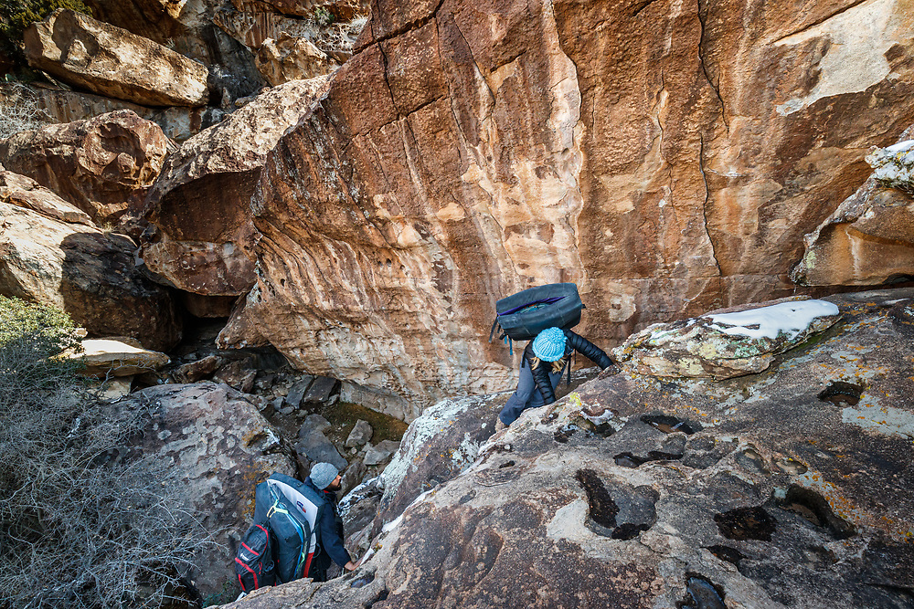 Sarah Hepola and guide Jacob Garza carrying bouldering pads to climbing site, Hueco Tanks State Park & Historic Site, El Paso, Texas. USA.
