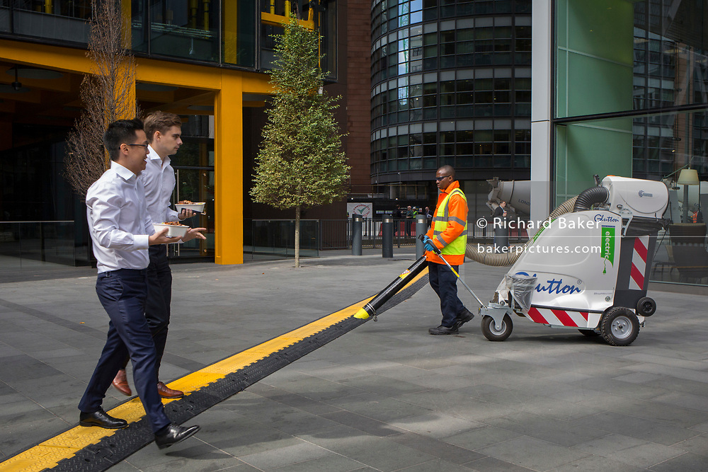 A contract street cleaner keeps the plaza free of litter and  crosses a yellow line that covers hazardous electrical cabling at Leadenhall in the City of London, (aka The Square Mile) the capital's financial district, on 2nd September 2019, in London, England.